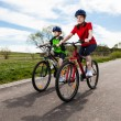 Girl and boy biking - Stock Photo