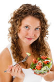 Young woman eating vegetable salad isolated on white background — Stock Photo
