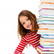 Girl peeking behind pile of books on white background - Stock Photo