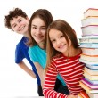 Students peeking behind pile of books on white - Stock Photo