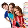 Students peeking behind pile of books on white — Stock Photo