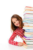 Girl peeking behind pile of books on white background — Stock Photo
