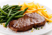 Grilled steak, French fries and green beans — Stock Photo