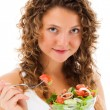 Young woman eating vegetable salad isolated on white background — Stock Photo #23367796