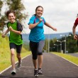 Healthy lifestyle - mother and kids running outdoor - Stockfoto