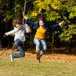 Girl and boy running, jumping in park - ストック写真
