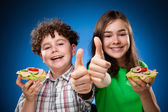 Kids eating big sandwich showing OK sign — Stock Photo