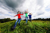 Active family - mother and kids running, jumping outdoor — Stock Photo