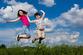女の子と男の子のランニング、ジャンプ屋外 — ストック写真