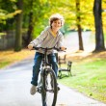 Urban biking - teenage boy riding bike in city park — Stock Photo