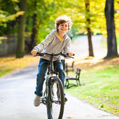 Urban biking - teenage boy riding bike in city park — Stock Photo