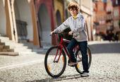 Městská cyklistika - dospívající chlapec a kolo v městě — Stock fotografie