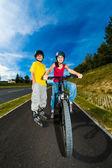 Healthy lifestyle - teenage girl and boy biking, rollerblading — Stock fotografie