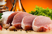 Porc cru sur la planche à découper et légumes — Photo