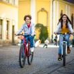 Urban biking - teens riding bikes in city park — Stock Photo #31620191