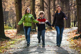 Active family - mother and kids walking, running outdoor — Stock Photo