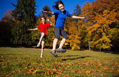 Girl and boy running, jumping in park — Стоковое фото