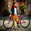 Urban biking - teenage girl and bike in city — Stock Photo