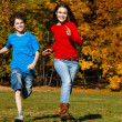 Girl and boy running, jumping in park — Stok fotoğraf