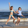 Stock Photo: Teenage girl and boy jumping, running on beach
