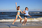 Teenage girl and boy jumping, running on beach — Stock Photo