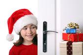 Girl with Santa's Hat peeking behind the door — Stock Photo