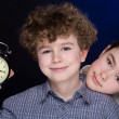 Stock Photo: Young boy and girl with alarm clock