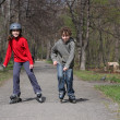 Young girl and boy on roller blades — Stock Photo
