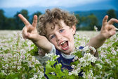 Boy sitting on green meadow — Stock Photo