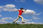 Jongen springen, uitgevoerd tegen blauwe hemel — Stockfoto