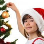 Young girl Santa decorating Christmas tree — Stock Photo #32749509