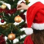 Young girl Santa decorating Christmas tree — Stock Photo #32749821