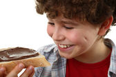 Kid eating bread with nut butter — Stock Photo