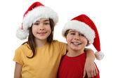 Pojke och flicka i santa hattar — Stockfoto