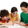 Mother helping her kids to do homework — Stockfoto