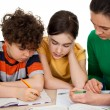 Mother helping her kids to do homework — Stock Photo