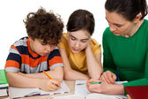 Mother helping her kids to do homework — Стоковое фото