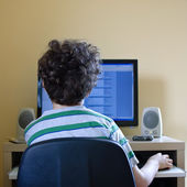 Young boy using computer at home — Stock Photo