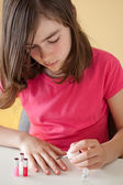Young girl painting her nails — Stock Photo