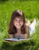 Girl lying on green meadow reading book — Stock Photo