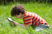Boy looking through magnifying glass — Stock Photo