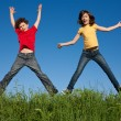 Girl and boy jumping against blue sky — Stockfoto