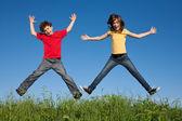 Niño y niña saltando contra el cielo azul — Foto de Stock