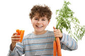 Boy holding fresh carrots — Stock Photo