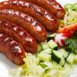 Grilled sausages with chips and vegetables — Stock Photo
