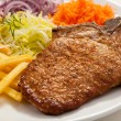 Grilled chop pork, french fries and vegetable salad — Стоковая фотография
