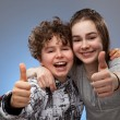 Boy and girl showing thumbs up sign — Stock Photo