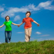Girl and boy jumping against blue sky — Stock Photo