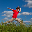 Boy jumping against blue sky — Stock Photo