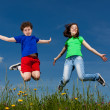 Girl and boy jumping outdoor — Stock Photo